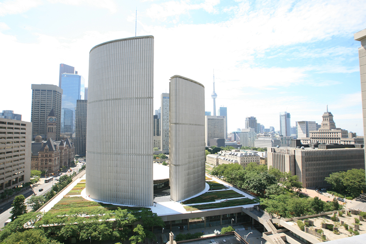 Toronto City Hall building surrounded by green roof modules, the city of Toronto in the background.